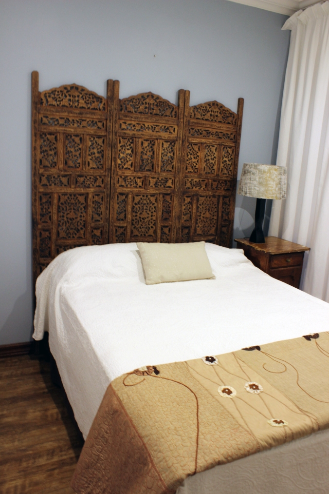 Neutral coloured bedroom with room devider as headboard